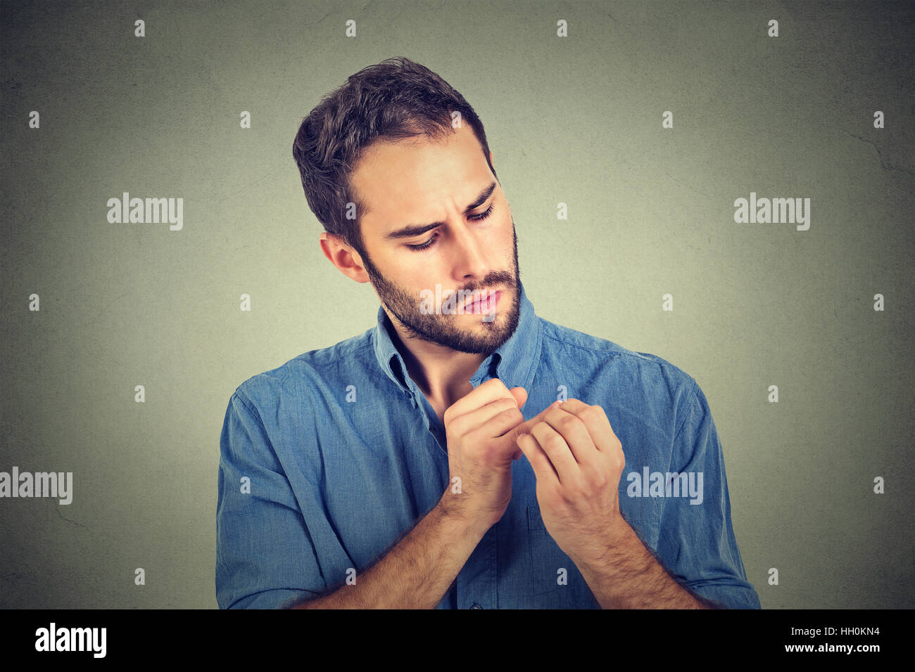 man looking at hands nails obsessing about cleanliness germs isolated on gray background. Emotion facial expression - Stock Image