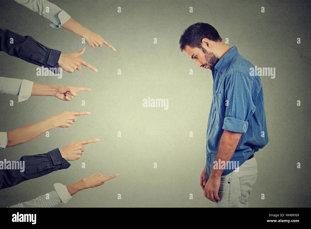 Concept of accusation guilty person man. Side profile sad upset man looking down many fingers pointing at him - Stock Image