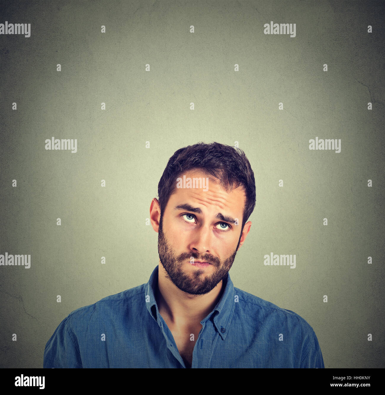 Portrait closeup funny confused skeptical man thinking looking up isolated on gray wall background with copy space - Stock Image