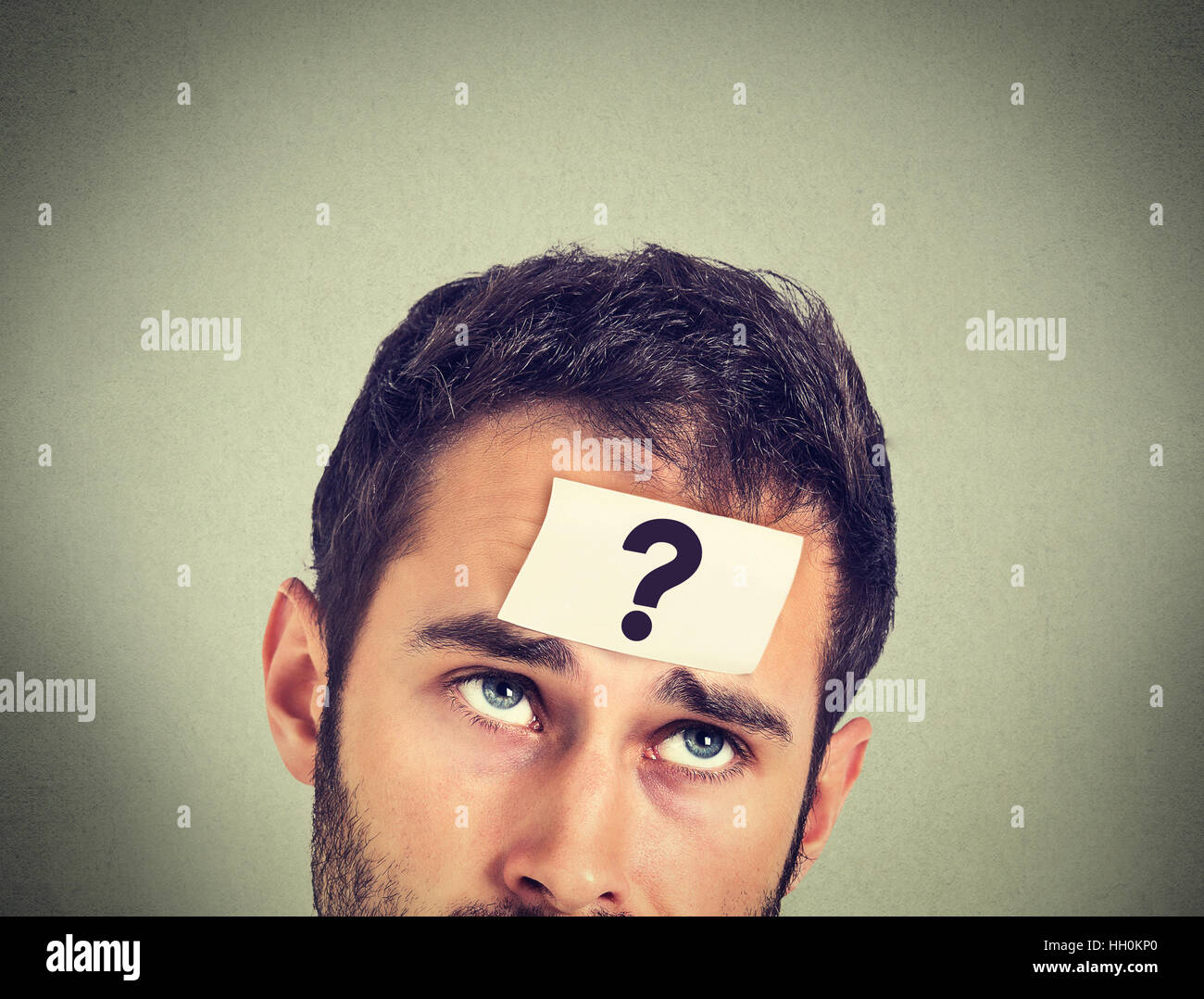 thinking man with question mark on gray wall background - Stock Image