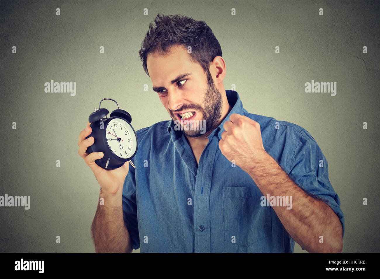 Portrait upset angry young man screaming at alarm clock isolated on gray wall background. Employee running late. - Stock Image