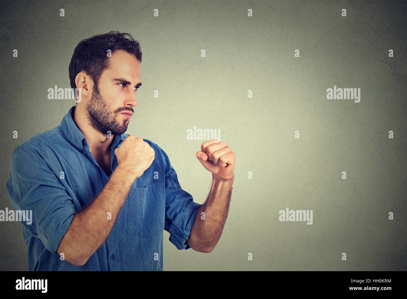 Angry young man clenching his fists - Stock Image