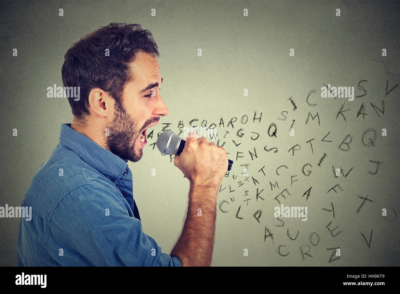 Young man singing in microphone with alphabet letters coming out of his mouth. Communication, information, intelligence - Stock Image