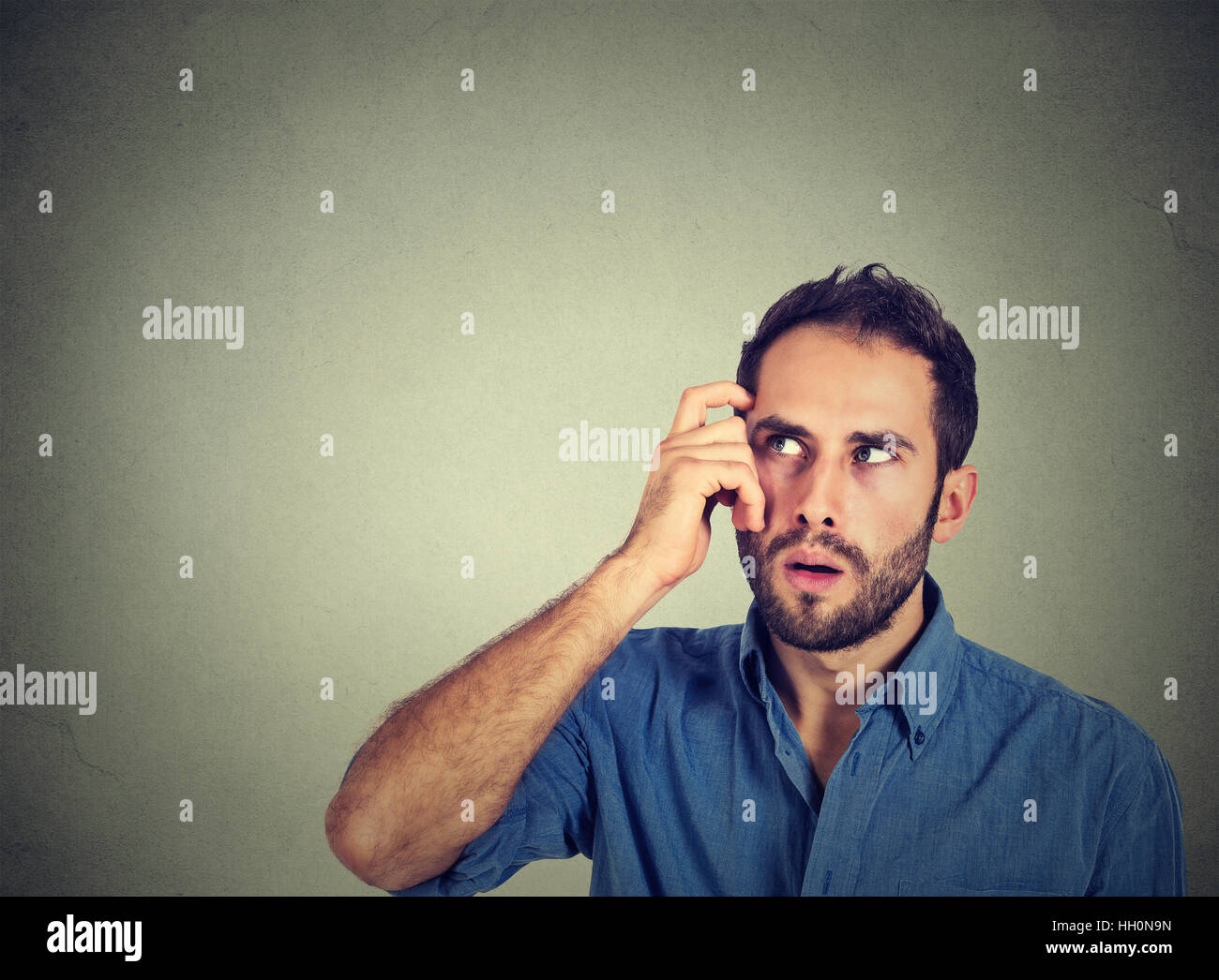 Closeup portrait young man scratching head, thinking deeply about something, looking up, isolated on grey wall background. - Stock Image