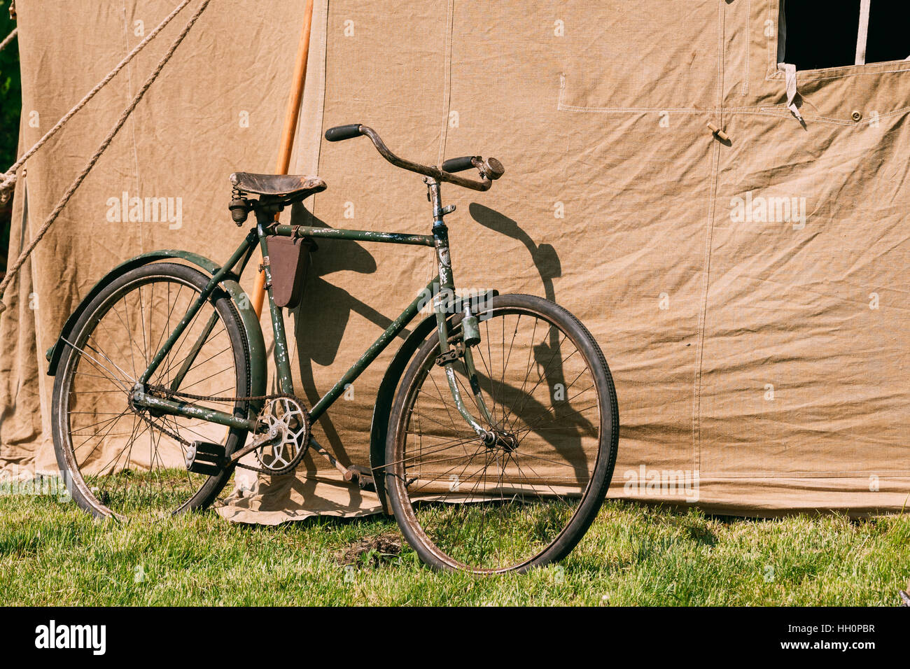 The Old Rarity Bicycle Parked Next To The Large Soviet Military Canvas Khaki Tent On Green Grass In Sunny Summer - Stock Image