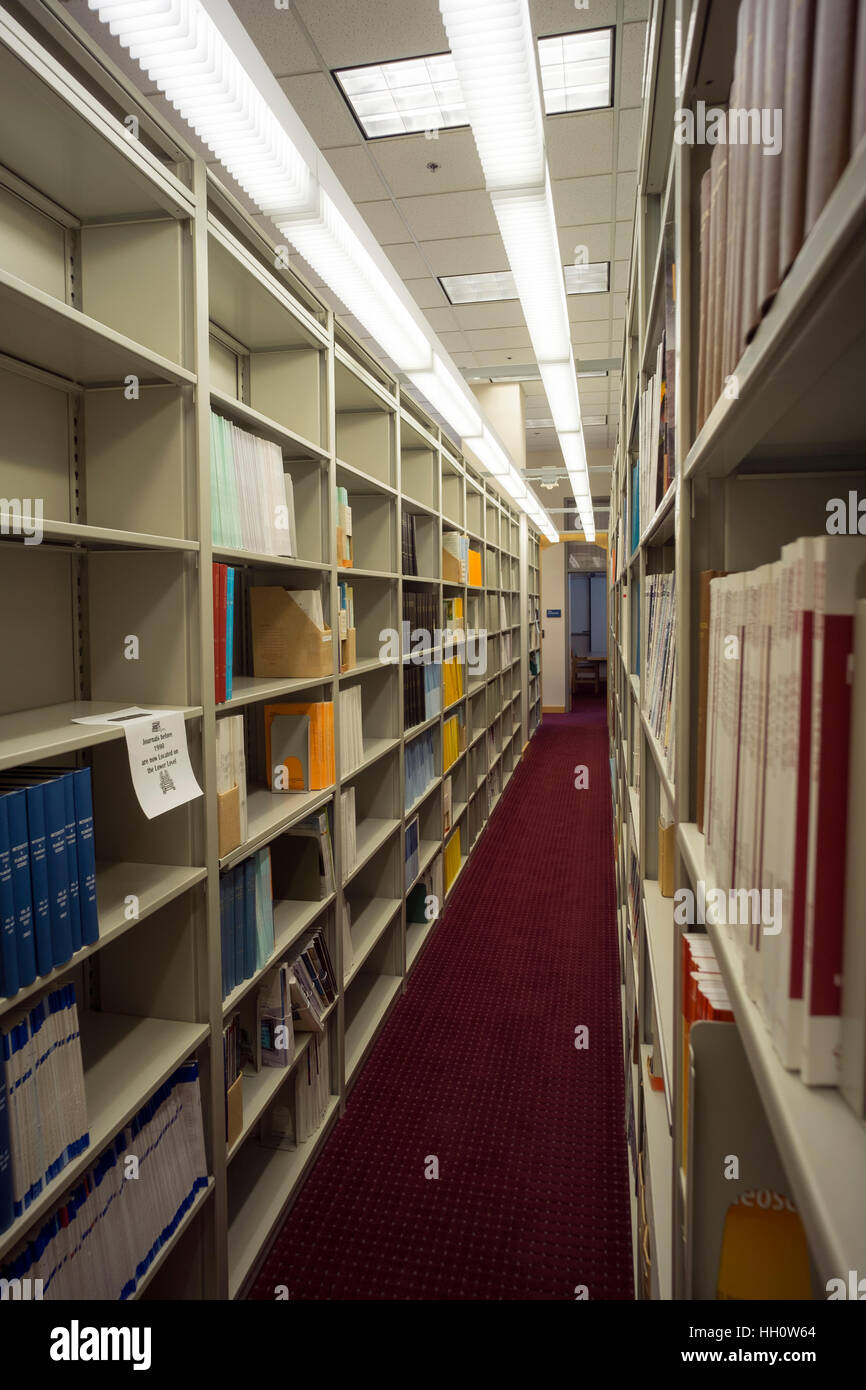 Books on the book shelves at the library. - Stock Image