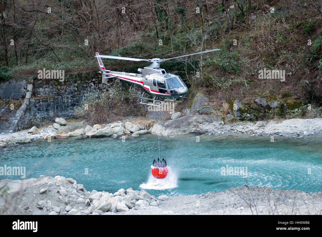 Fire fighting helicopter collecting water in a suspended bucket below the chopper from a mountain river to dowse - Stock Image