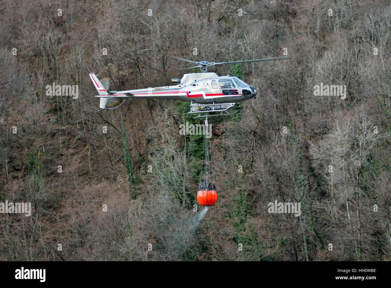 Helicopter transporting a bucket full of water suspended below the plane as it fights a mountain fire in the wilderness - Stock Image
