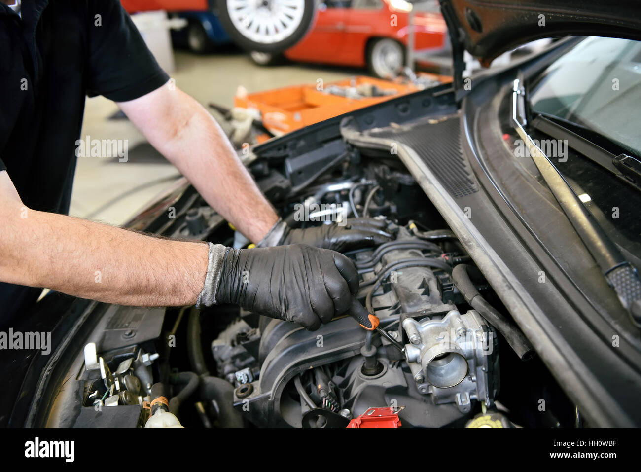 Gloved hands of a mechanic working on a car engine as he services or repairs it in a workshop or garage - Stock Image
