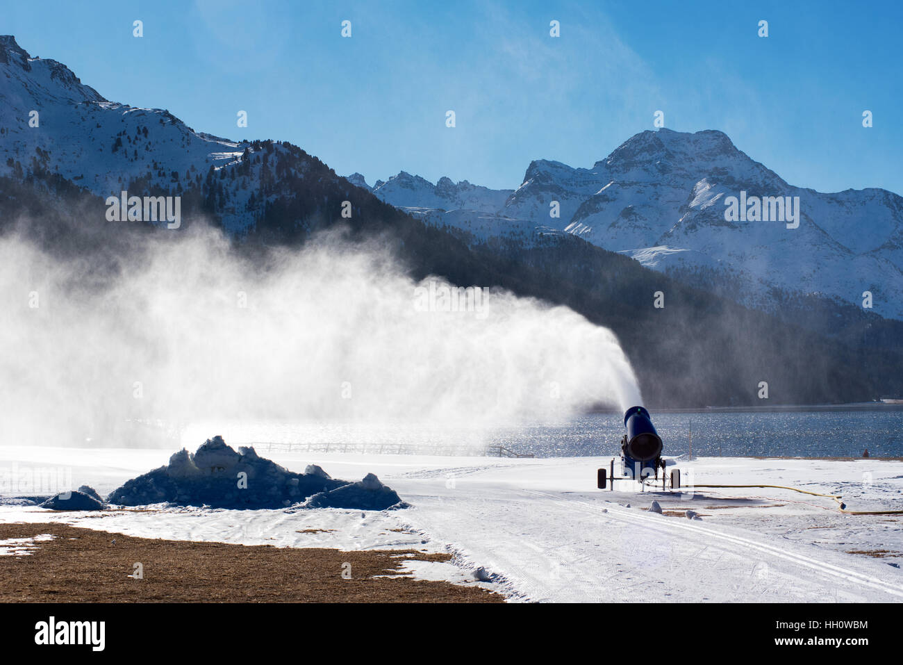 Snow canon or gun blowing artificial snow onto a piste or run at a mountain ski resort when the weather has been - Stock Image
