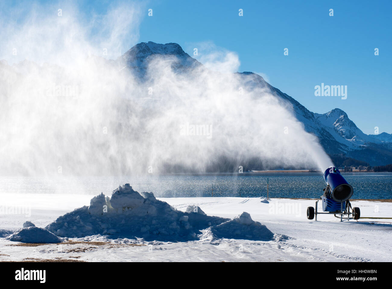 Artificial snow blown by snow gun standing near water on snowbound ground in sunny day with blue sky - Stock Image