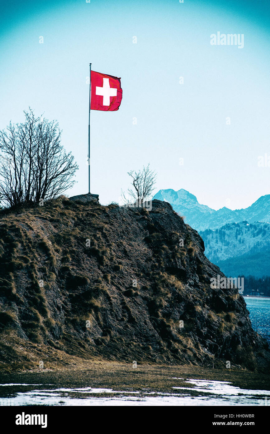 Swiss flag flying above a mountain in the alps covered in light winter snow on a cold sunny blue sky day - Stock Image