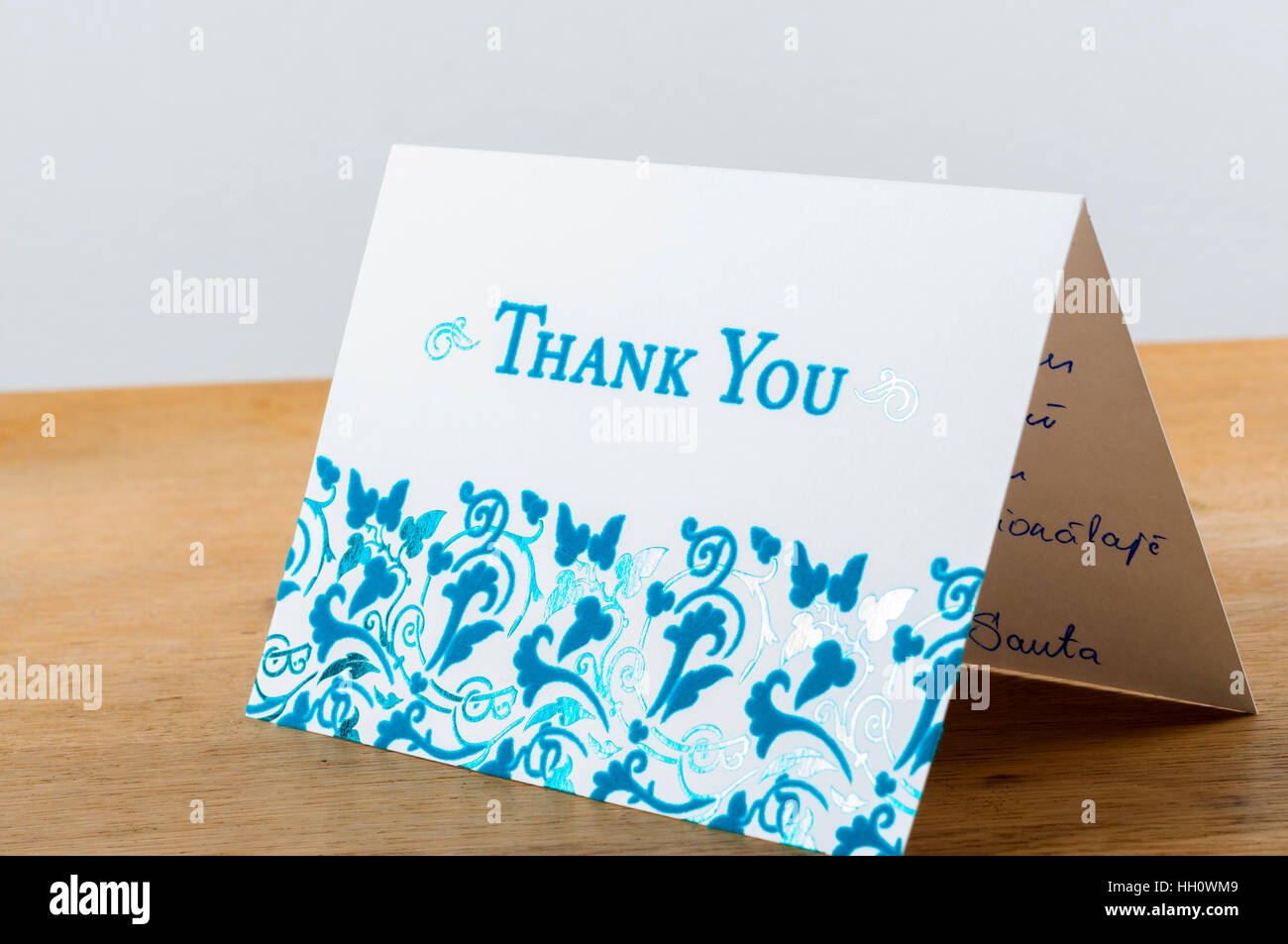White thank you card with blue letters with note written by hand - Stock Image