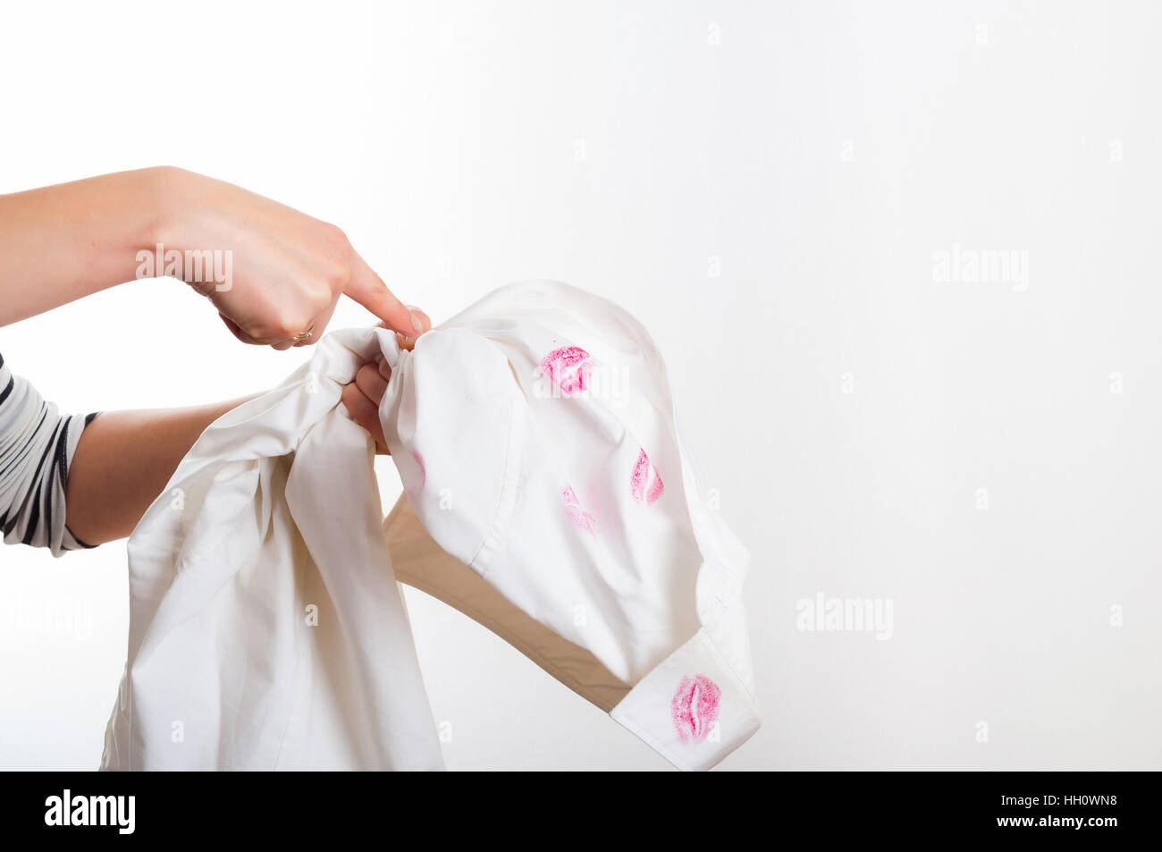 Woman pointing on white shirt with red lipstick marks suspecting of cheating - Stock Image