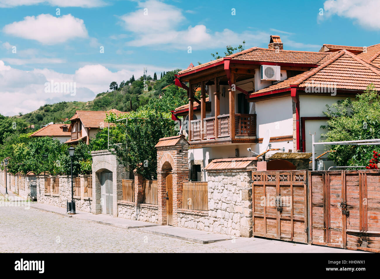 The White Beautiful Private Country House With Red Tile Roof And Wooden  Balcony At The Cosy Paved Street In Sunny Summer Under Blue