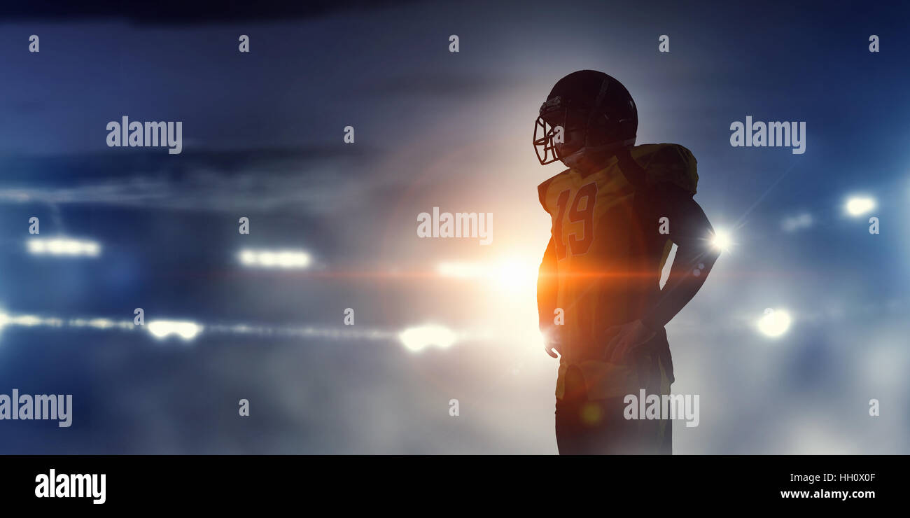 American football player silhouette against lights of stadium. Mixed media - Stock Image