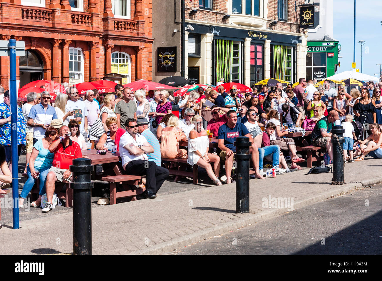 England, Ramsgate. Seafront, summer heat wave, audience, people sitting in sunshine outside bar, watching (unseen) - Stock Image