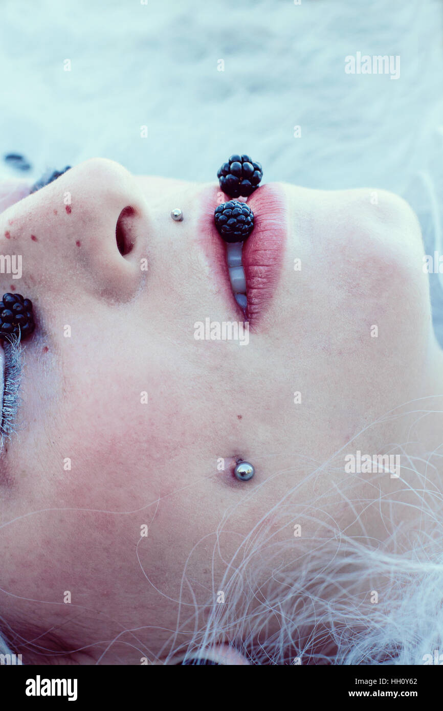 Young woman mouth close up with blackberries - Stock Image