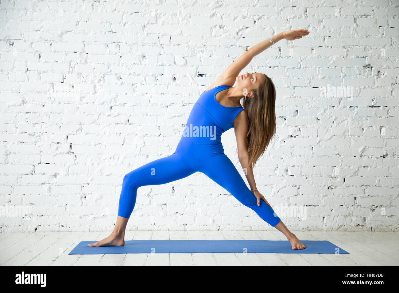 Young attractive woman in Reverse Warrior pose, white studio bac - Stock Image