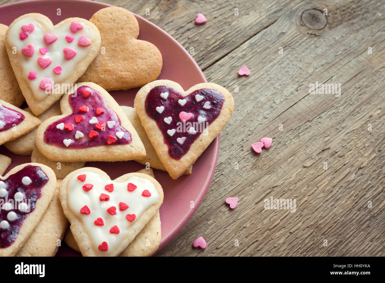 Glazed heart shaped cookies for Valentine's day - delicious homemade natural organic pastry, baking with love - Stock Image