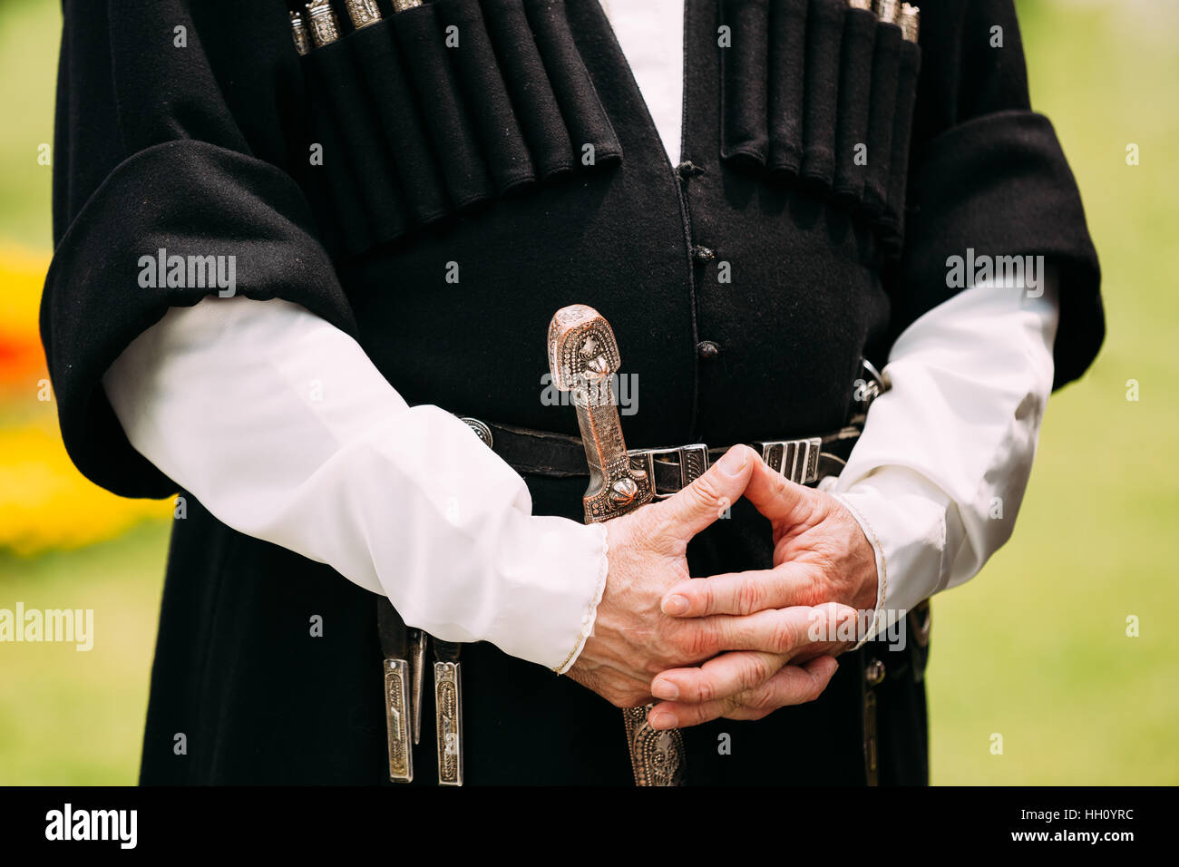 Close Up Hands Of Elder Georgian Man In National Clothes. Culture Of Georgia Country. On His Belt Dagger Hanging. - Stock Image
