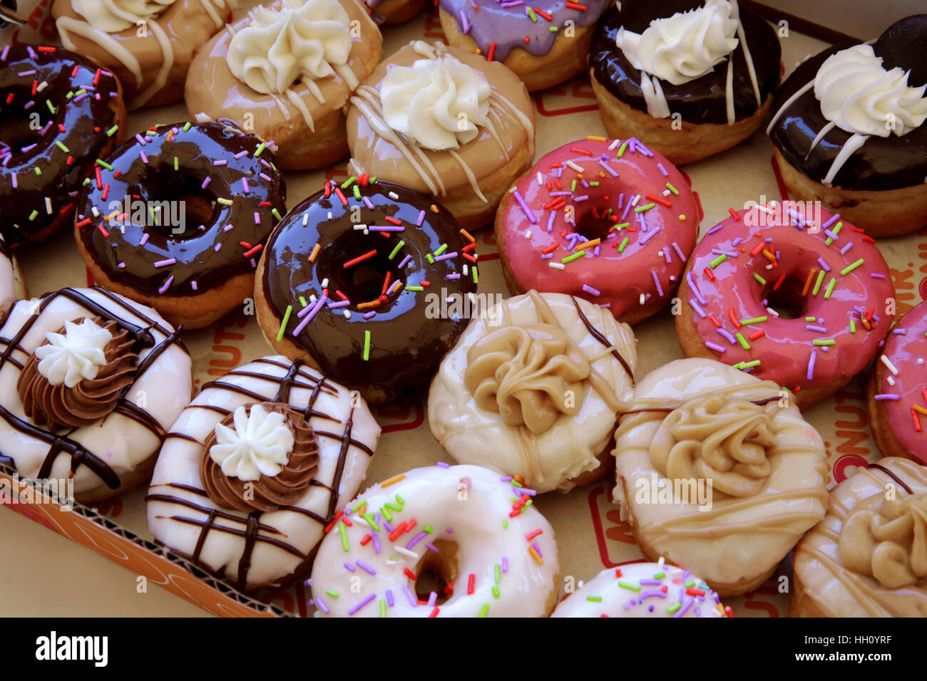 Sugar coated colorful doughnuts - Stock Image