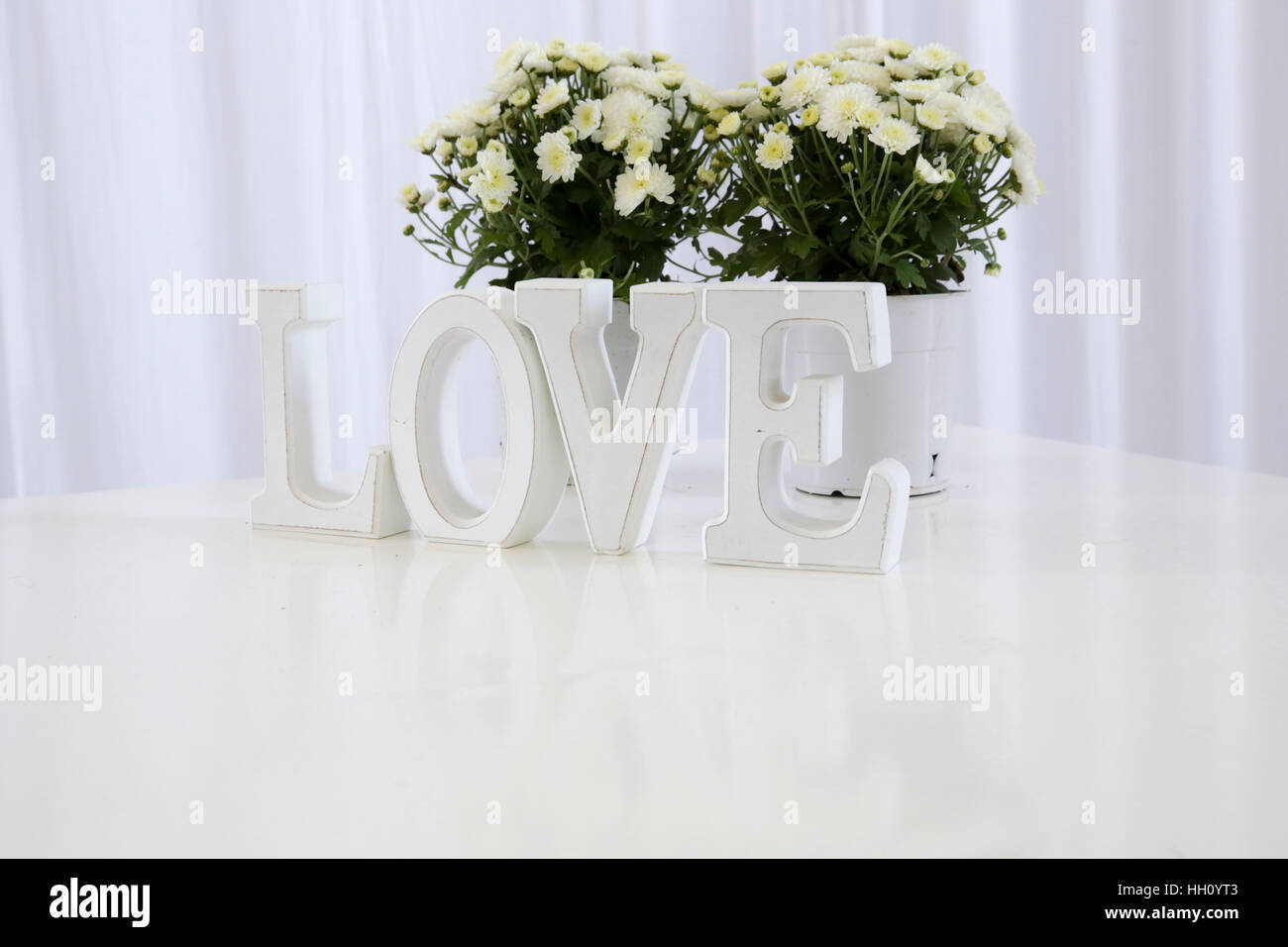 white LOVE text with white flowers - Stock Image