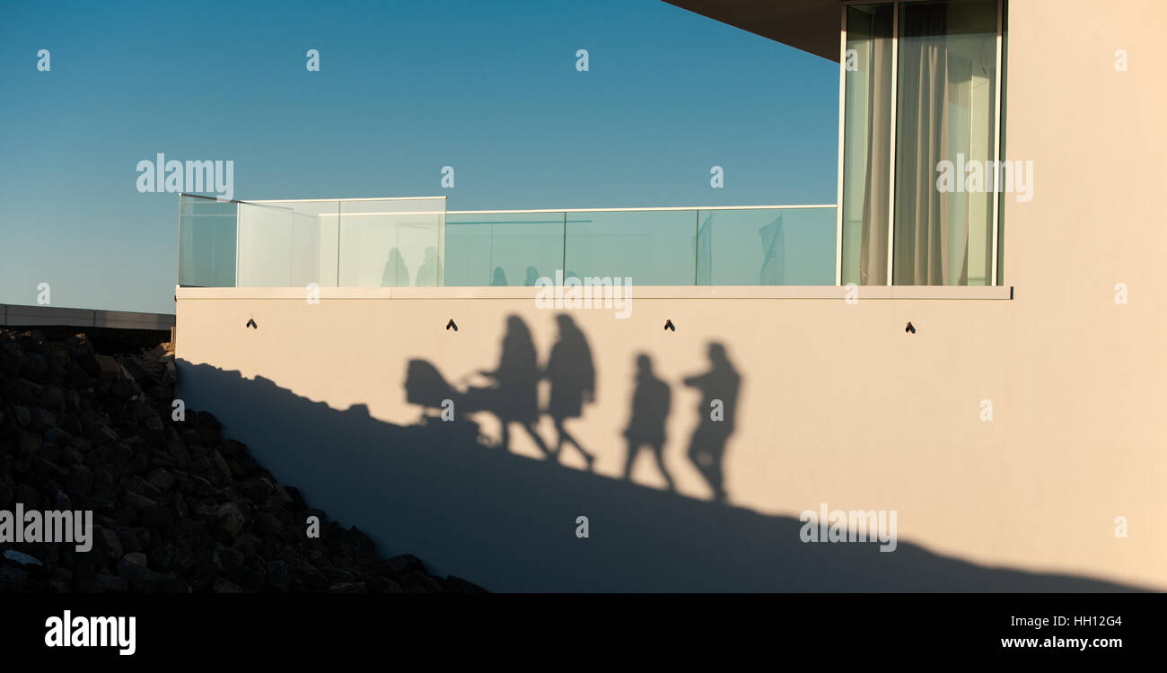 Shadow on a wall of a family consisting of father, mother two children and a pram - Stock Image
