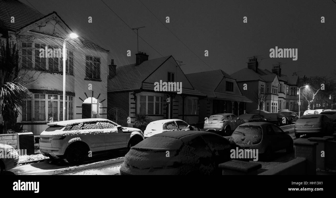 Snow Falling at Night on a Suburban Street - Stock Image