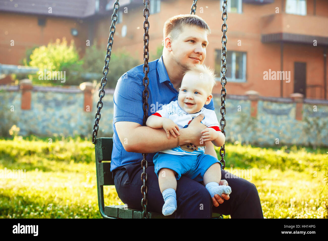 father, hugs a child who laughs - Stock Image