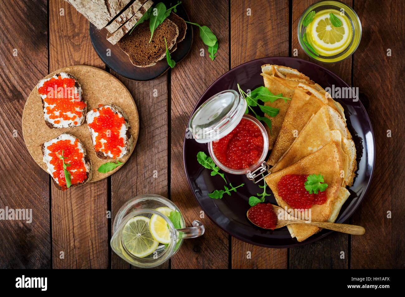 Pancakes with red caviar on plate. Russian cuisine. Maslenitsa. Flat lay. Top view Stock Photo