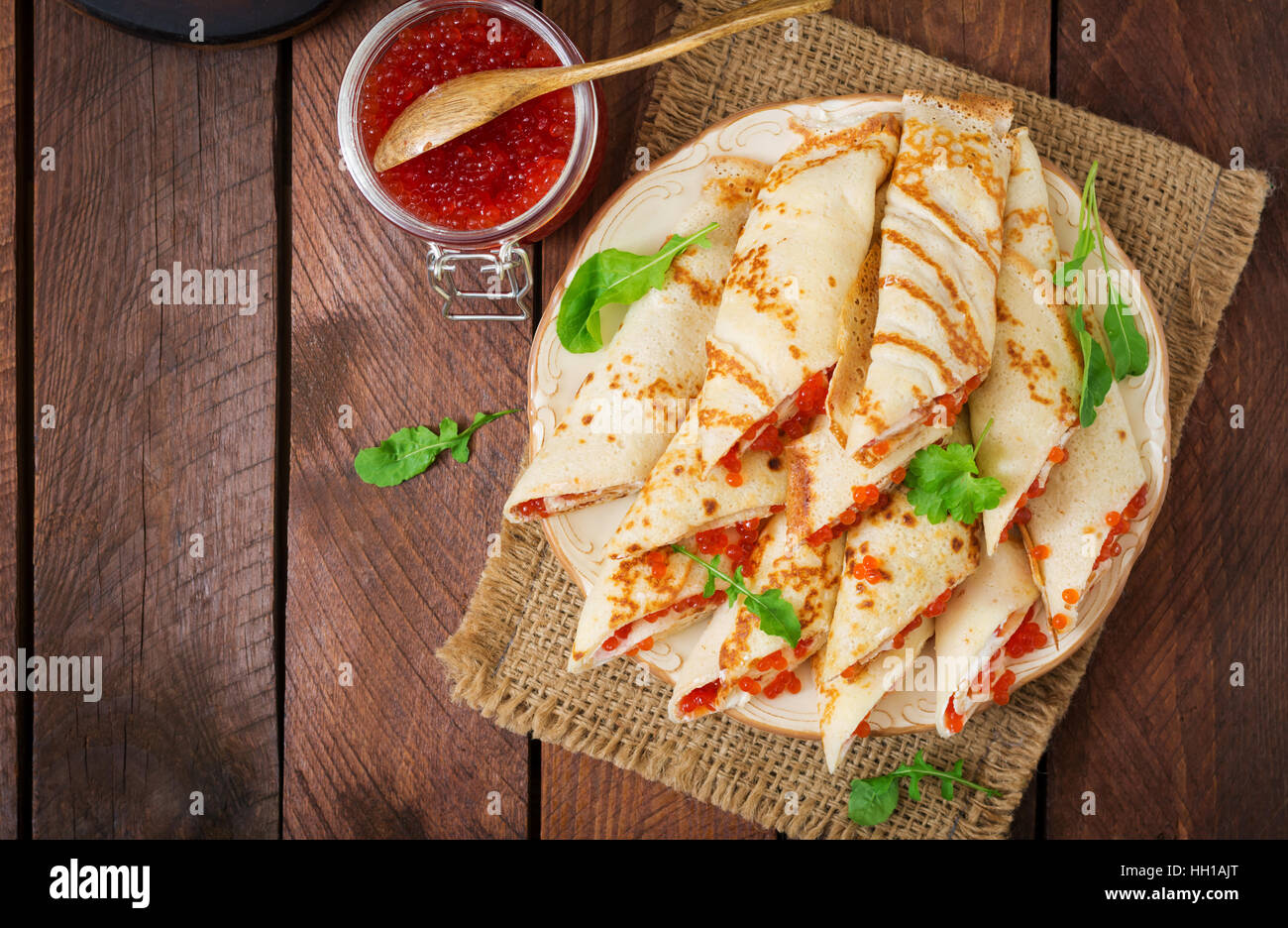 Pancakes with red caviar on plate. Russian cuisine. Maslenitsa Stock Photo