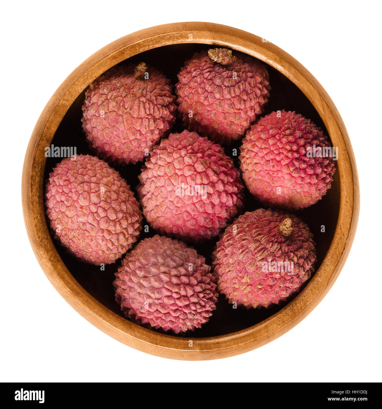 Lychee or litchi fruits in wooden bowl. Unpeeled ripe red Litchi chinensis, also called liechee, liche, lizhi or - Stock Image