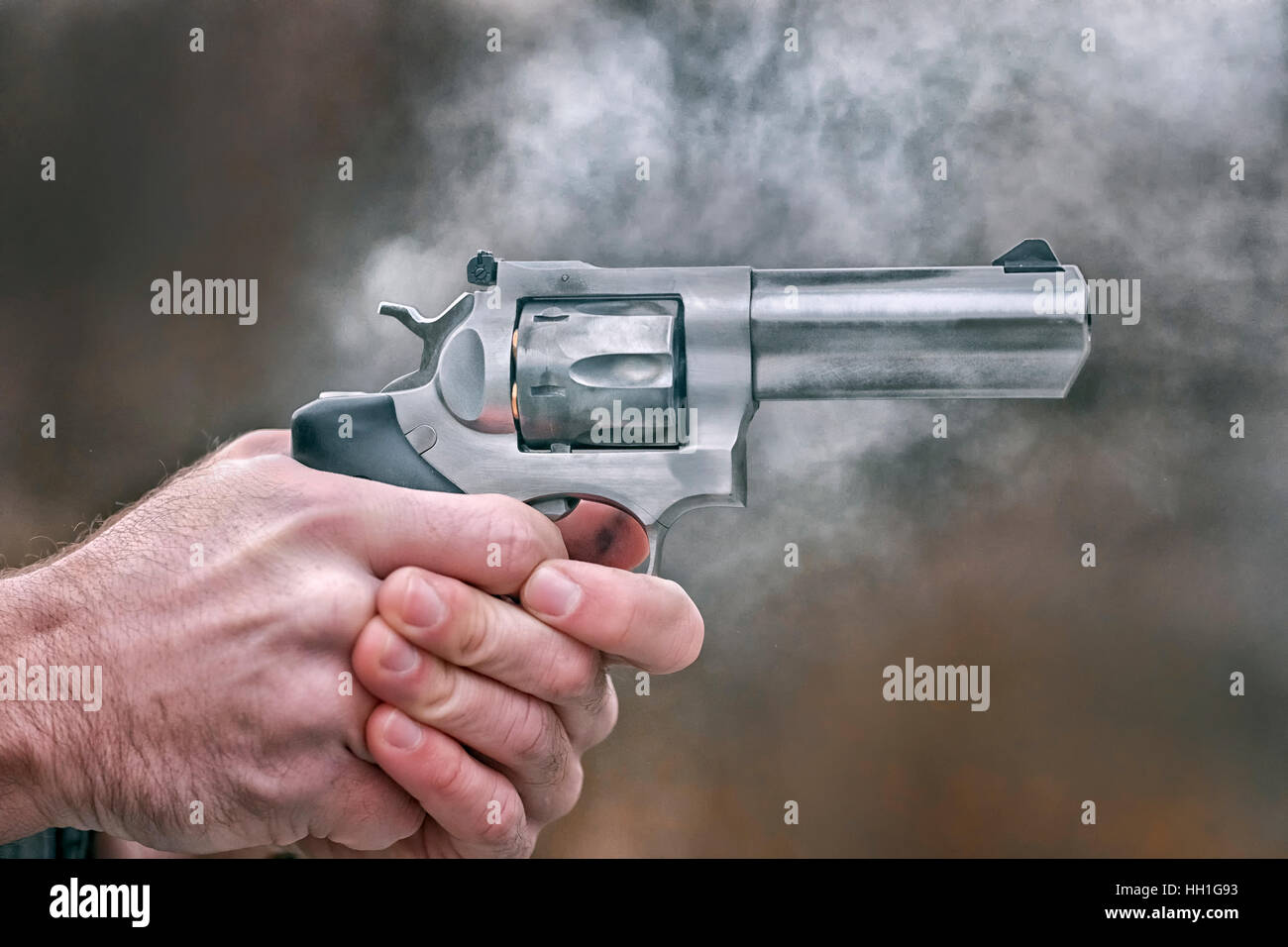 Revolver handgun surrounded with smoke moment after being discharged - Stock Image