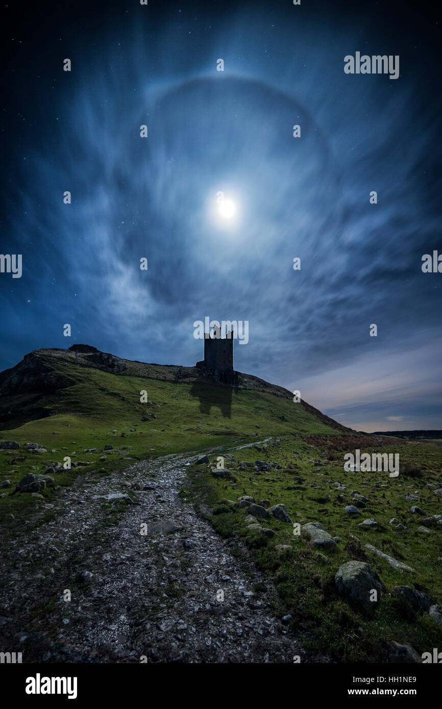 A 22° lunar halo over Dunstanburgh Castle on Northumberland coast in the UK - Stock Image