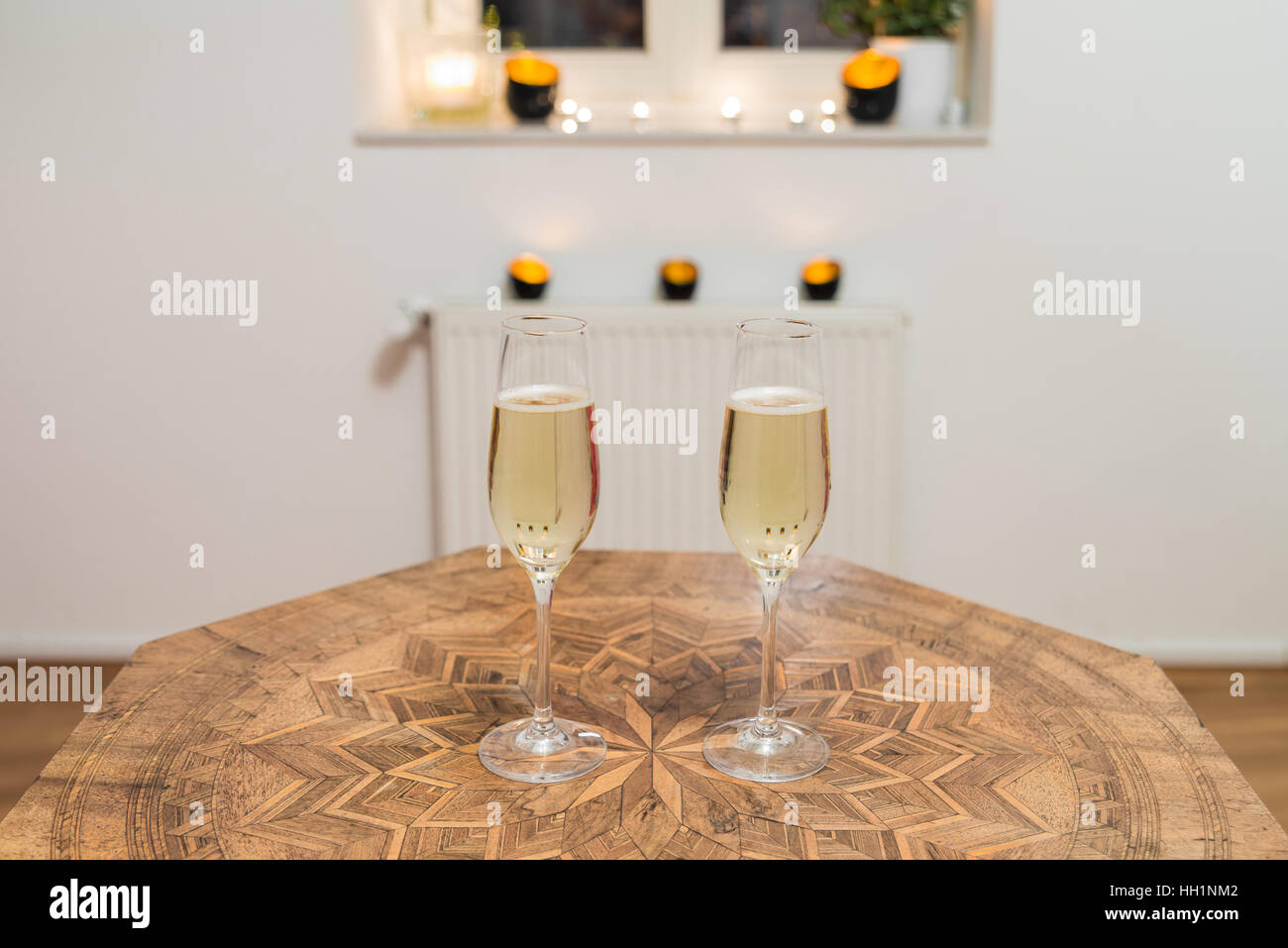 Two glasses filled with champagne on a antique table - Stock Image