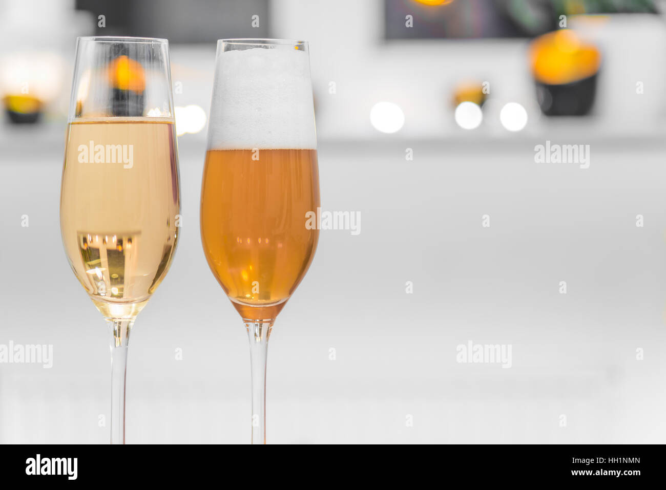 Closeup of two glasses filled with champagne and beer - Stock Image