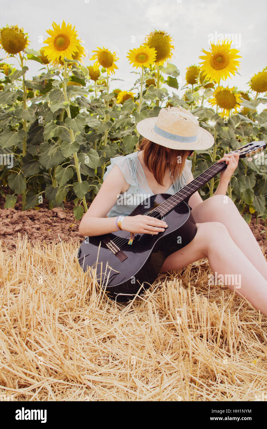 Young woman in a field of sunflowers at summer playing her black guitar - Stock Image