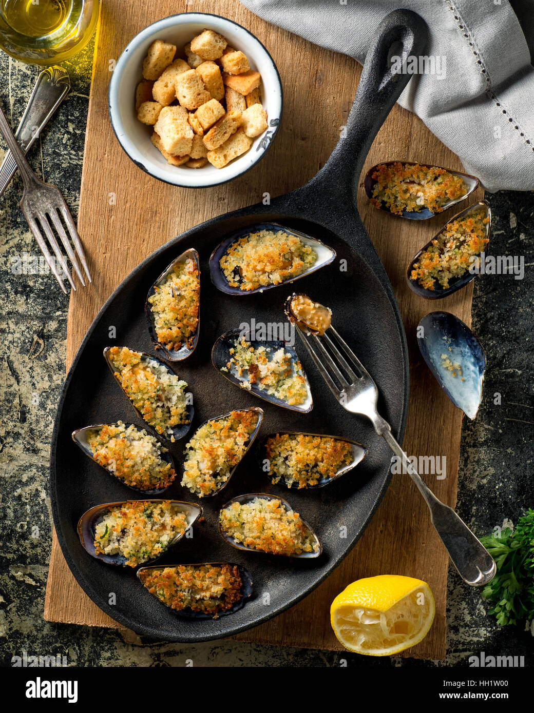 Delicious baked mussels on an iron skillet with breadcrumbs, lemon, parsley, garlic, and olive oil. - Stock Image