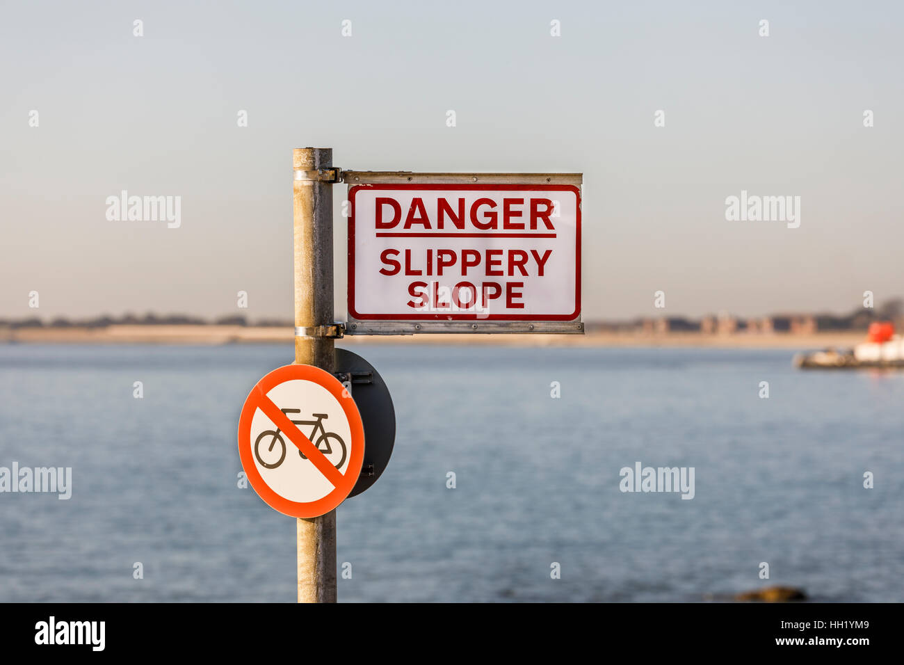 Warning sign 'Danger, slippery slope' and round no cycling road sign on the seafront promenade at Southsea, - Stock Image