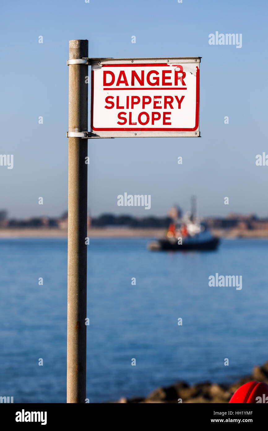 Warning sign 'Danger, slippery slope' by the shore on the seafront at Southsea, Portsmouth, Hampshire, southern - Stock Image