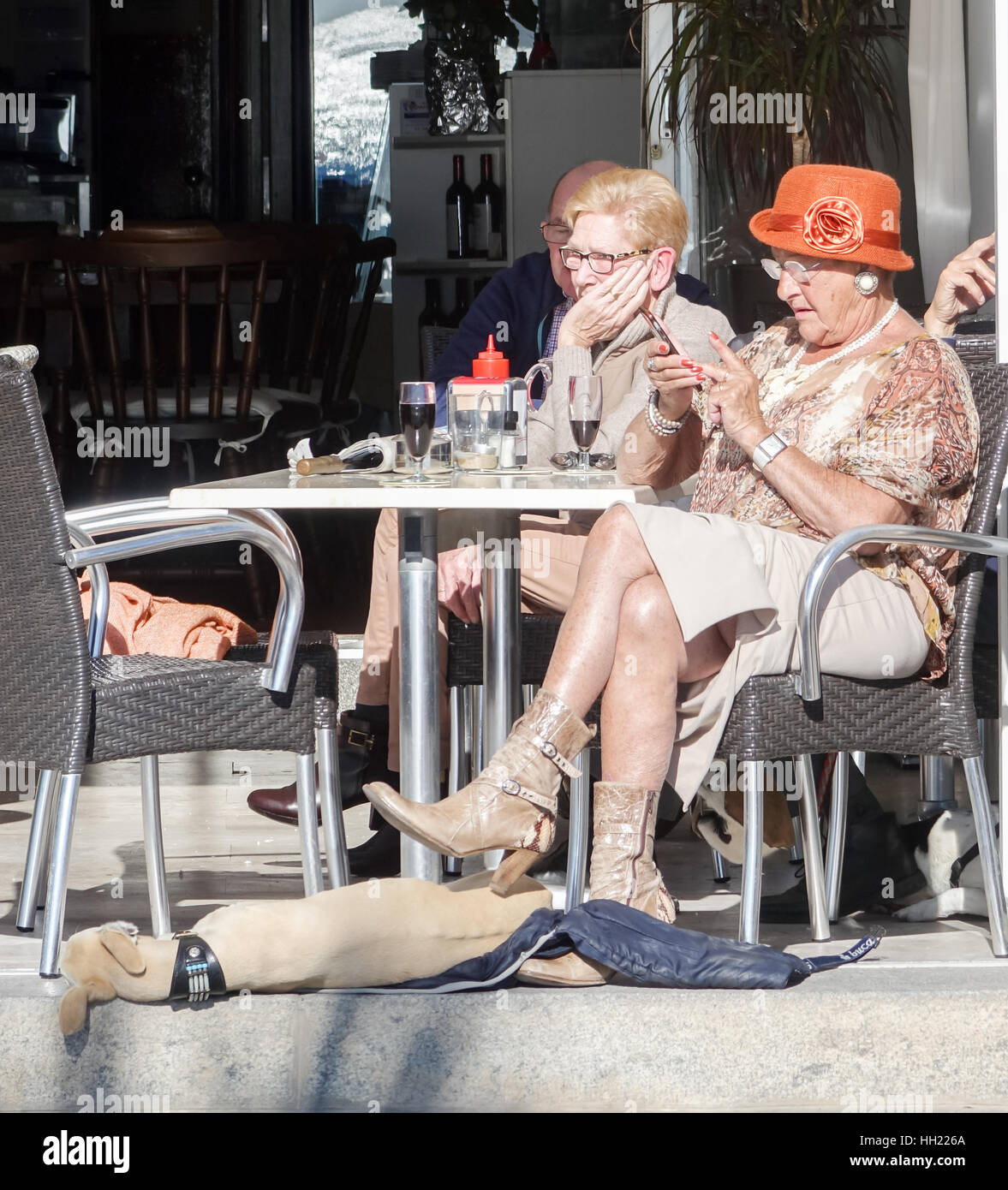 Elderly women sitting outside a bar on Levante beach, Benidorm, Alicante Province, Spain with nice bright hat using - Stock Image