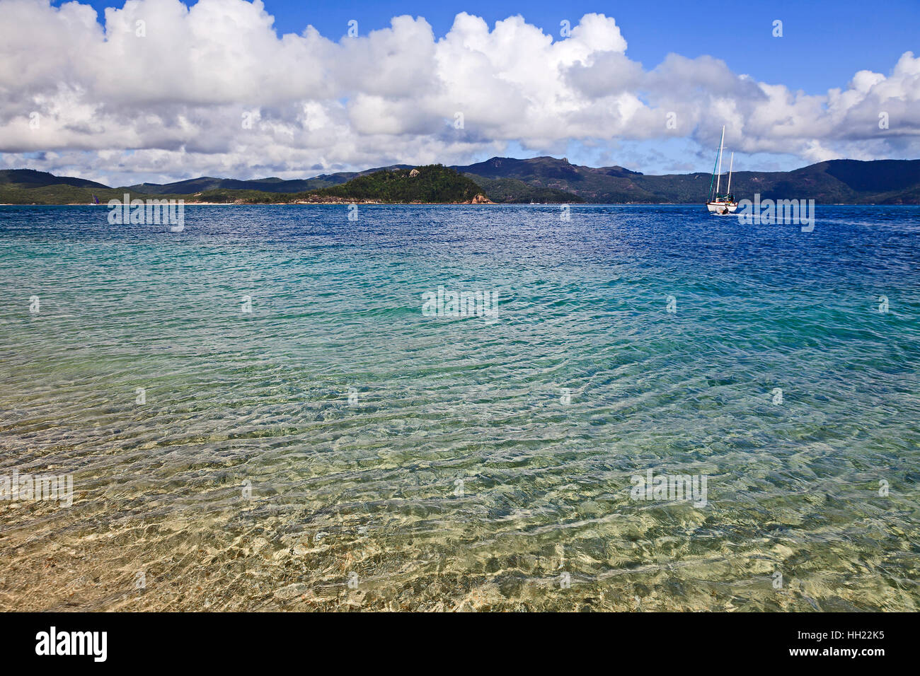 Clean transparent water in coral island lagoon of whitesunday islands. Lonely white yachs anchored off-shore in Stock Photo