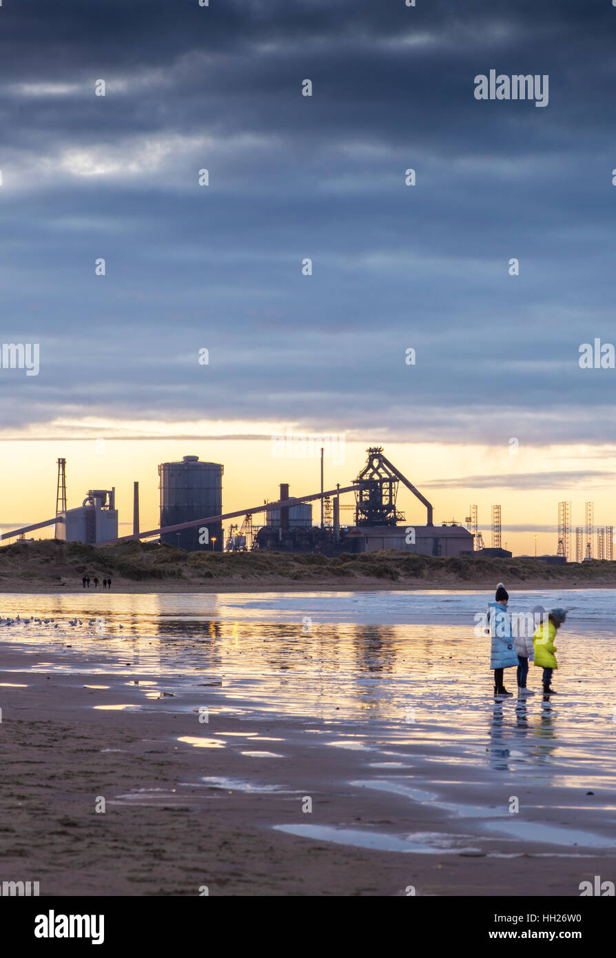 Children play on the Coatham Beach close to the redundant site of Redcar steelworks. - Stock Image