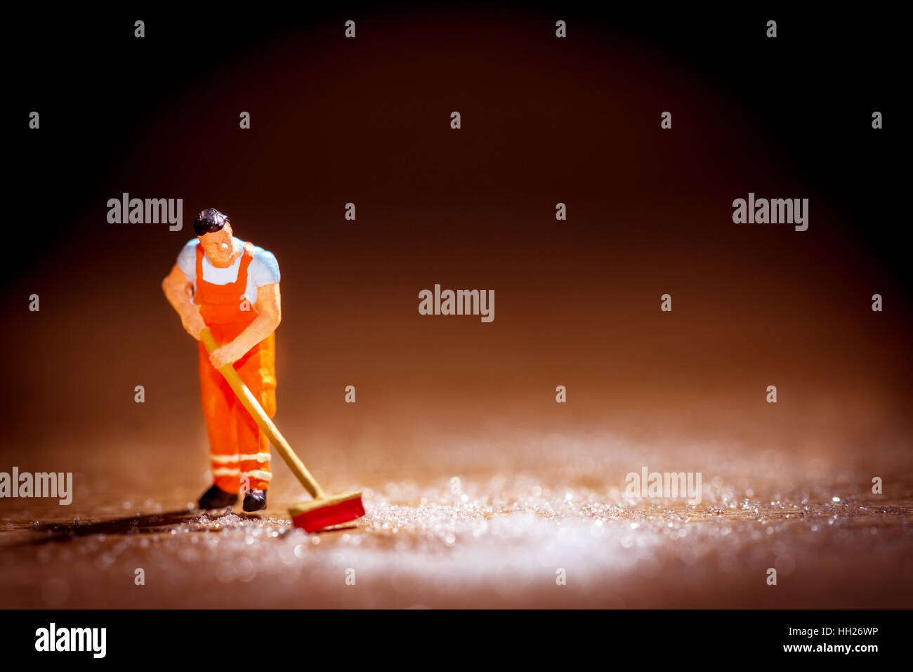 Conceptual image of a man sweeping up. - Stock Image