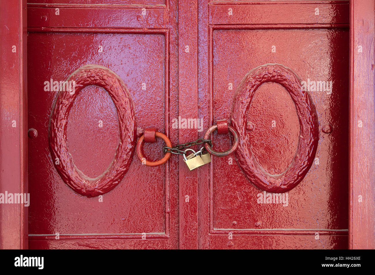 Red painted door with a padlock and chain - Stock Image