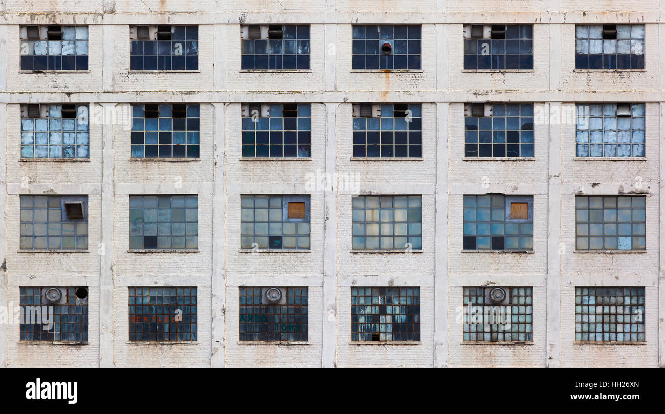 Windows in a facade of an old neglected factory building - Stock Image