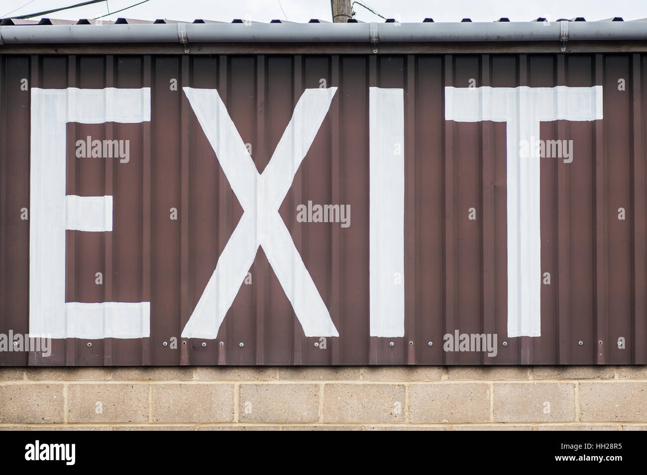Large white painted letters show the way to the Exit - Stock Image