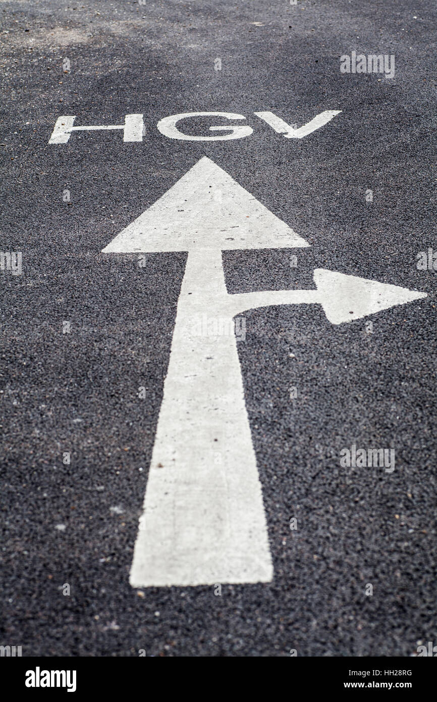 HGV ahead sign with white painted arrow on the tarmac - Stock Image