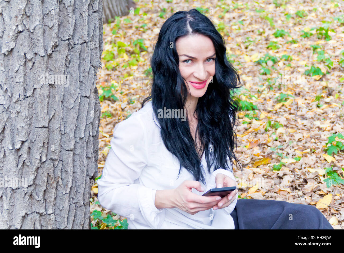 Caucasian brunette writing sms by cellular in autumn park - Stock Image